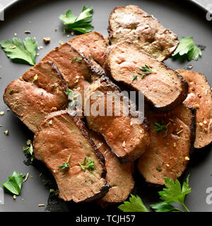 Close up of grilled sliced beef liver on plate over black stone background. Cooked liver(offal) from beef meat. - Stock Image