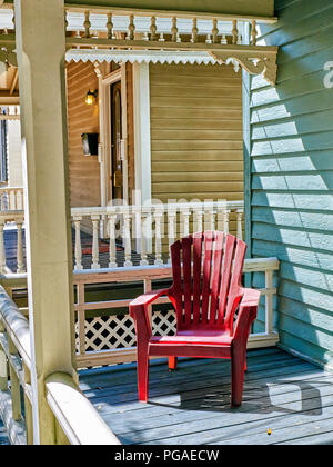Empty single red chair on a front porch in a residential neighborhood of Montgomery Alabama, USA. - Stock Image