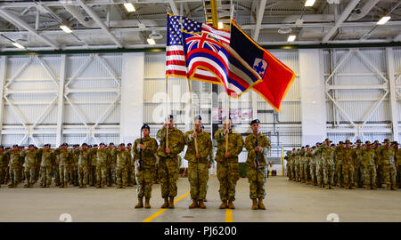 Soldiers from Alpha and Bravo Troops, 1st Squadron, 299th Cavalry Regiment, and elements of the 29th Infantry Brigade Combat Team, both from the Hawaii Army National Guard render a salute alongside the color guard team during their deployment ceremony at the Kalaeloa Army Aviation Support Facility on August 26, 2018. The 1-299th CAV will be deploying to Sinai, Egypt supporting the Multinational Force and Observers while the 29th IBCT will be deploying to Kosovo in support of Multinational Battle Group East Kosovo Forces (KFOR). (U.S. Army National Guard photo by Sgt. 1st Class Theresa Gualdara - Stock Image
