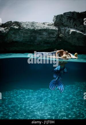 Merman and mermaid with sea monster - Stock Image