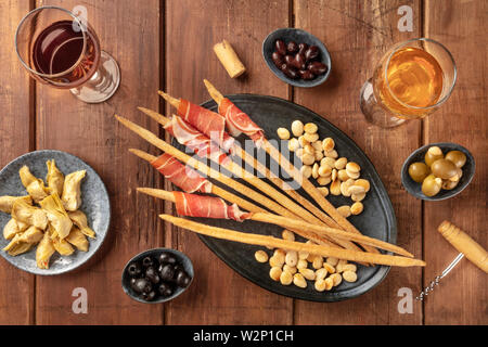 Italian antipasti. Grissini, parma ham, almonds, olives, and wine on a dark rustic wooden background - Stock Image