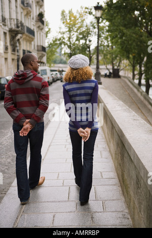 Rear view of African couple walking - Stock Image