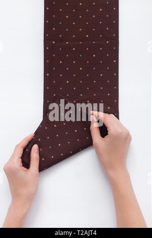 Hands of woman folding brown fabric - Stock Image