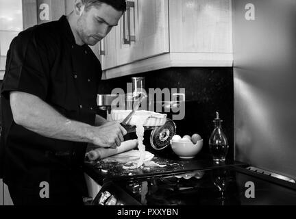 Handsome male chef, dressed in black jacket, cuts off excess pastry from a dish - Stock Image
