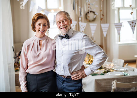 A portrait of a senior couple standing indoors in a room set for a party. Copy space. - Stock Image