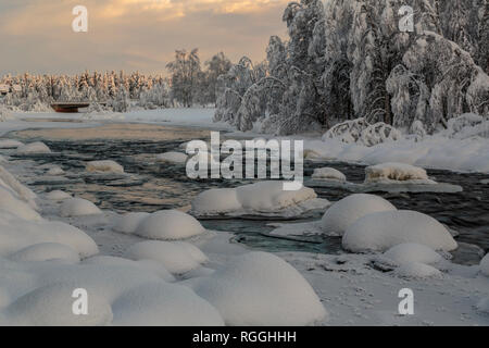 Wassara river in Gällivare at winter season, open water, nice color in the sky reflecting in the water, rocks covered in snow, Gällivare, Swedish Lapl - Stock Image