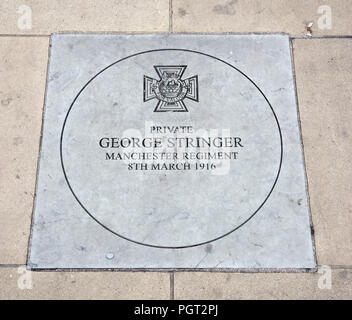 Plaque at foot of Manchester England war memorial showing Victoria Cross awarded Private George Stringer Manchester Regiment 8th March 1916 - Stock Image