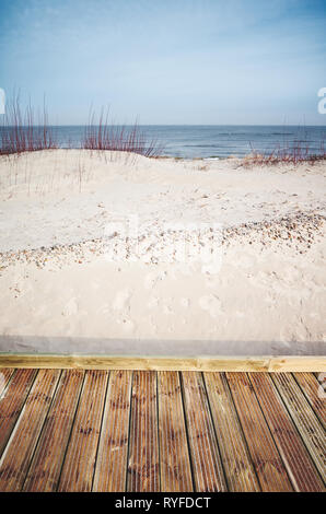 Wooden boardwalk by a beach, color toned picture. - Stock Image