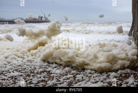Brighton, UK. 12th Mar, 2019. Sea foam is blown like snow on to Brighton beach as Storm Gareth arrives in Britain and Ireland with wind speeds forecast to reach up to 70 mph in some areas Credit: Simon Dack/Alamy Live News - Stock Image