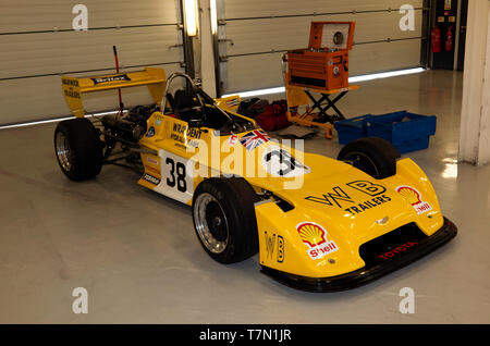 Three-quarter front view of Hugh Price's Yellow, 1977, Chevron B38 Formula 3 Car, in the  Pit garages, during the 2019 Silverstone Classic Media Day. - Stock Image