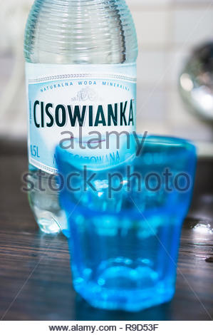 Poznan, Poland - November 10, 2018: Polish Cisowianka water in a bottle with blue glass in soft focus foreground. - Stock Image