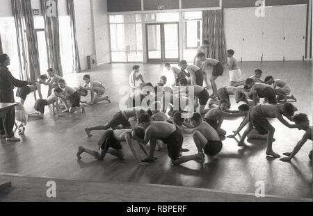 1950s, historical, shirtless schoolboys wrestling each other in a PE class inside the school hall at the John Colet County Secondary school, Wendover, Bucks, England, UK. - Stock Image