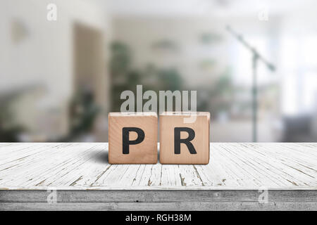PR sign on a worn table in a bright room with green plants and a microphone - Stock Image