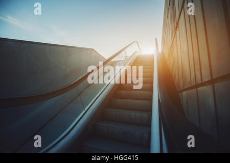 City street outdoor grungy modern escalator goes up to sun and blue sky, rusty metal tiled wall on the right, view - Stock Image