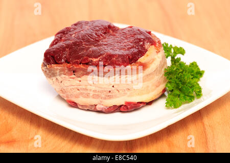 Two 8oz filet mignon beef steaks wrapped with bacon on a wood cutting board. - Stock Image
