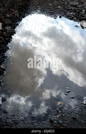 Cracked and broken asphalt pothole on the surface of a crumbling road. Rain water puddle collects in the cracked - Stock Image