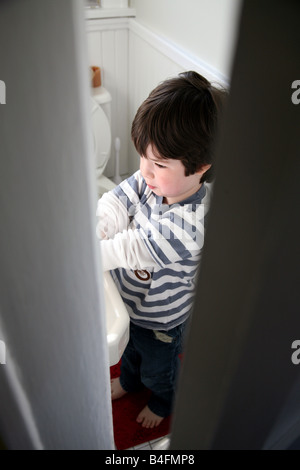 Boy washing hands, viewed through crack in bathroom door - Stock Image