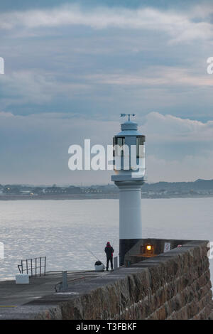 Penzance, Cornwall, UK. 9th Apr, 2019. UK Weather. It was mild and warm for the sunrise at Penzance this morning for this fisherman on the harbour walls at Penzance. Credit: Simon Maycock/Alamy Live News - Stock Image