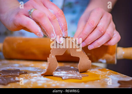 Preparations for Christmas, the hands of a woman hold a piece of cake for gingerbread cookie stars almost ready to bake - Stock Image
