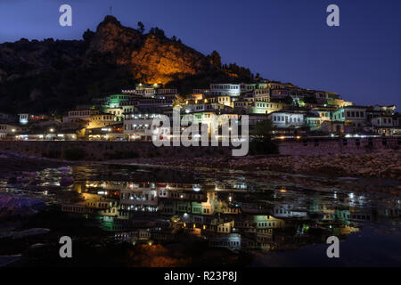 Night view of the houses of Berat, Albania known as the one thousand window city. Reflection of lights in river. Castle overviews the scene - Stock Image