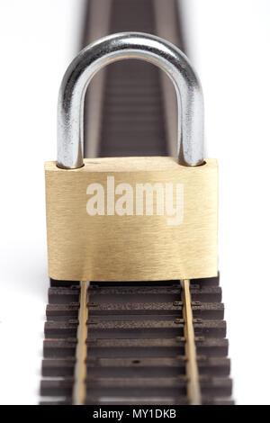 Closed padlock put on a single rail closeup isolated on white. - Stock Image