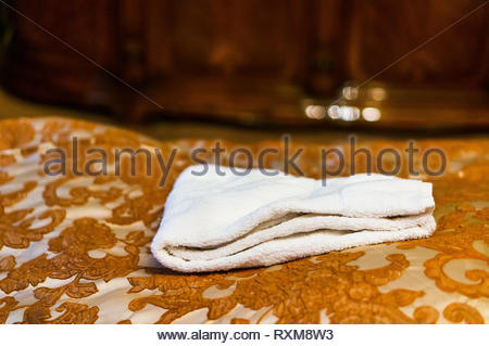 Fresh white towels laying on a bed sheet with flower pattern. - Stock Image
