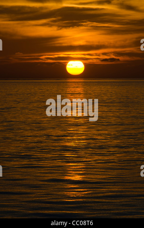 The golden sun drops below the clouds just before hitting the horizon. The very calm waters create a sharp reflection - Stock Image