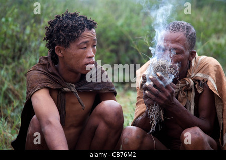Bushman making fire in the Kalahari desert near Ghanzi, Botswana, Africa - Stock Image