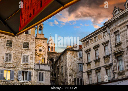 The bell and cathedral tower reflect the colorful clouds as the sun sets on People's Square at Diocletian's Palace in Split Croatia - Stock Image