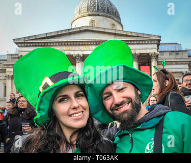London, UK. 17th Mar, 2019.   A couple pose in front of the National Gallery. Following the spectacular St Patrick's Day Parade earlier, people celebrate and watch performances on Trafalgar Square in the heart of London. Credit: Imageplotter/Alamy Live News - Stock Image