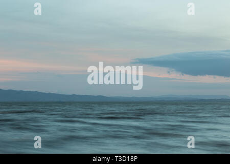 Close view of moving waves on a lake at dusk - Stock Image