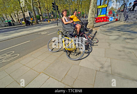 London, England, UK. Cyclists having a rest on a bench on the Victoria Embankment - Stock Image
