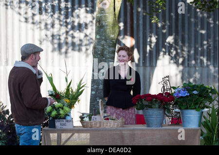Chichester, West Sussex, UK. 14th Sep, 2013. Goodwood Revival. Goodwood Racing Circuit, West Sussex - Saturday 14th September. A flower seller behind her stall sells grand prix roses. Credit:  MeonStock/Alamy Live News - Stock Image