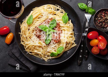 Spaghetti bolognese pasta with tomato and minced meat sauce, parmesan cheese and fresh basil. Red wine glass and cooking ingredients. Top view - Stock Image