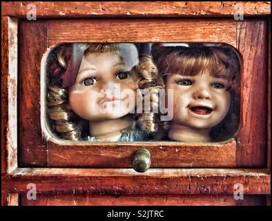The decapitated heads of two dolls look out from a wooden box. Macabre? Cruel? Maybe dollies that a child no longer plays with or wants to own? Childhood moves on? Photo © COLIN HOSKINS. - Stock Image