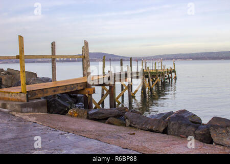 A small wooden pier used by the local yaucht club on The Esplanade at Holywood County Down. Belfast Lough and the distant County Antrim shore can be s - Stock Image