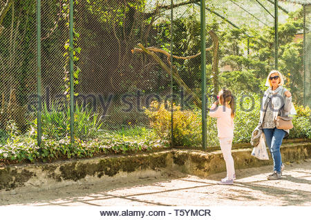 Poznan, Poland - April 18, 2019: Woman and girl standing by a grid cage with plants and birds in the old zoo on a warm sunny day. - Stock Image