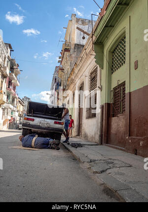 Mechanic working on an old American car in the back streets of Havana, Cuba - Stock Image