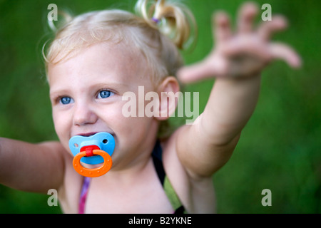 A two-year-old girl with a pacifier and pig tails reaches up while playing outdoors. - Stock Image