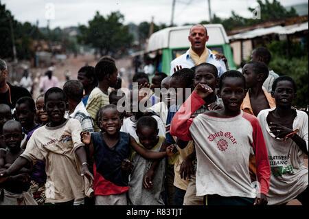 Mali, Africa. White caucasian mature volunteer enjoys escorting children in a rural village near Bamako. - Stock Image