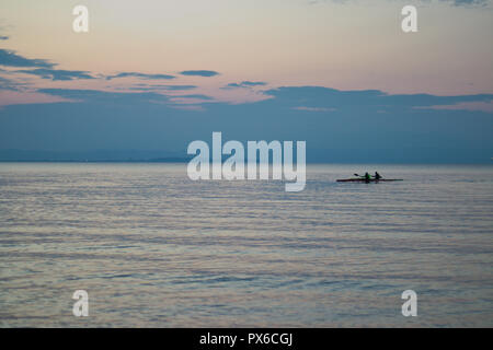 canoeist at the lake during sunset - Stock Image