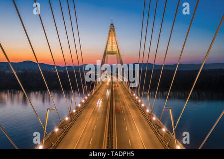 Budapest, Hungary - Aerial view of the beautiful cable-stayed Megyeri Bridge over River Danube with blue and orange sky after sunset - Stock Image