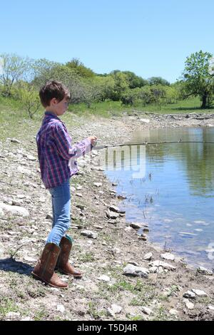 Child with short brown hair and cowboy boots fishing at the edge of a lake - Stock Image