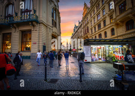 Tourists and local Czech enjoy a brilliant sunset outside a small shop in Republic square with the Tyn Towers of Old Town in view at Prague, Czechia - Stock Image