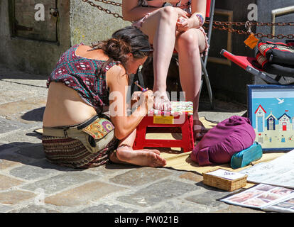 A young woman painting another young woman's foot with a Henna design or tattoo on St. Ives Harbour, St. Ives, Cornwall, England, UK - Stock Image