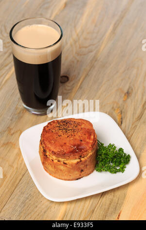 Trader Joe's Market Steak and Ale Meat Pie prepared from frozen with a pint of stout beer - Stock Image