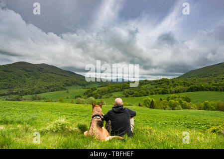 Active man sitting with dog in mountains, looking at view ad resting. - Stock Image