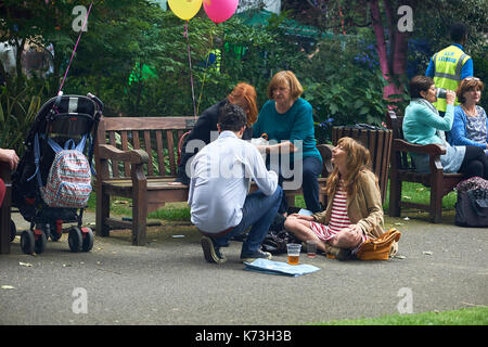 Young woman meditating on path next to park bench with people seated sitting in London, United Kingdom. - Stock Image