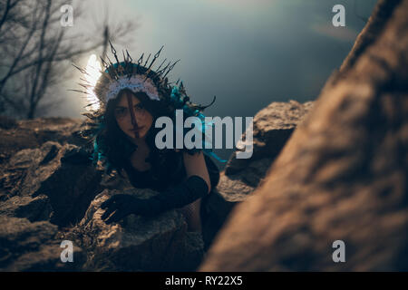 A young woman in the image of a fairy and a sorceress standing next to rocks over a lake in a black dress and a crown. - Stock Image