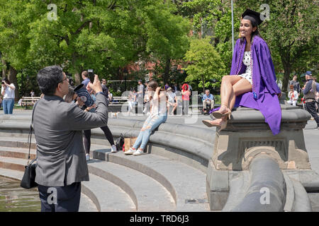 A man, likely a family member, takes a posed photo of an NYU graduate in her cap & gown, in Washington Square Park, Greenwich Village, New York City. - Stock Image